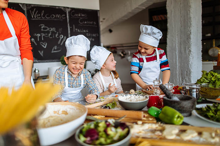 Photo of a group of children having fun during cooking class with a chef